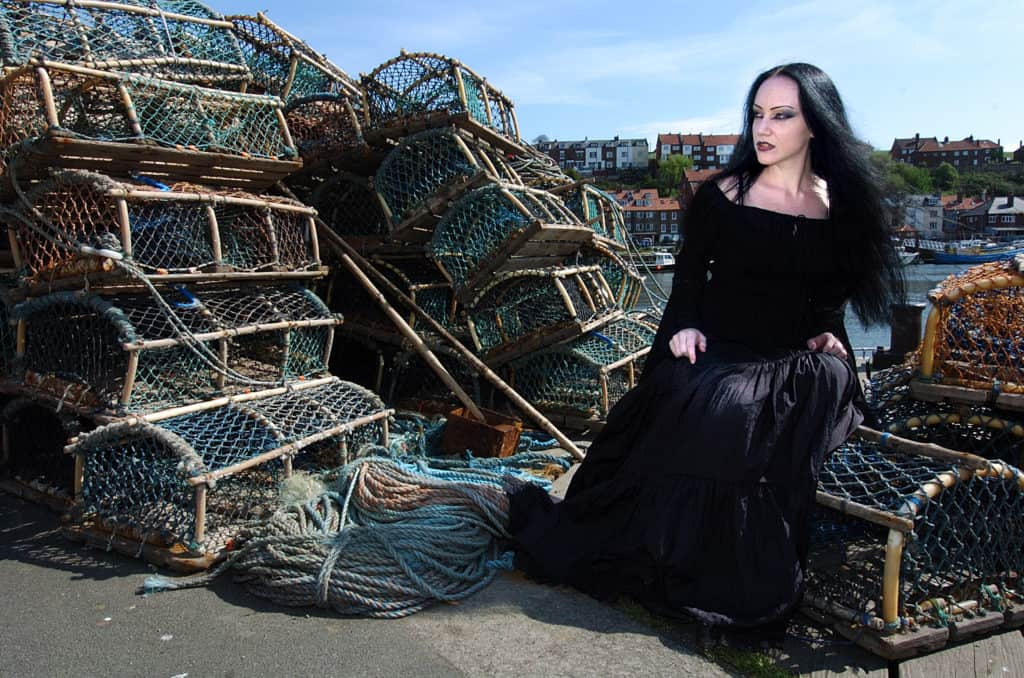 woman goth sitting by lobster traps