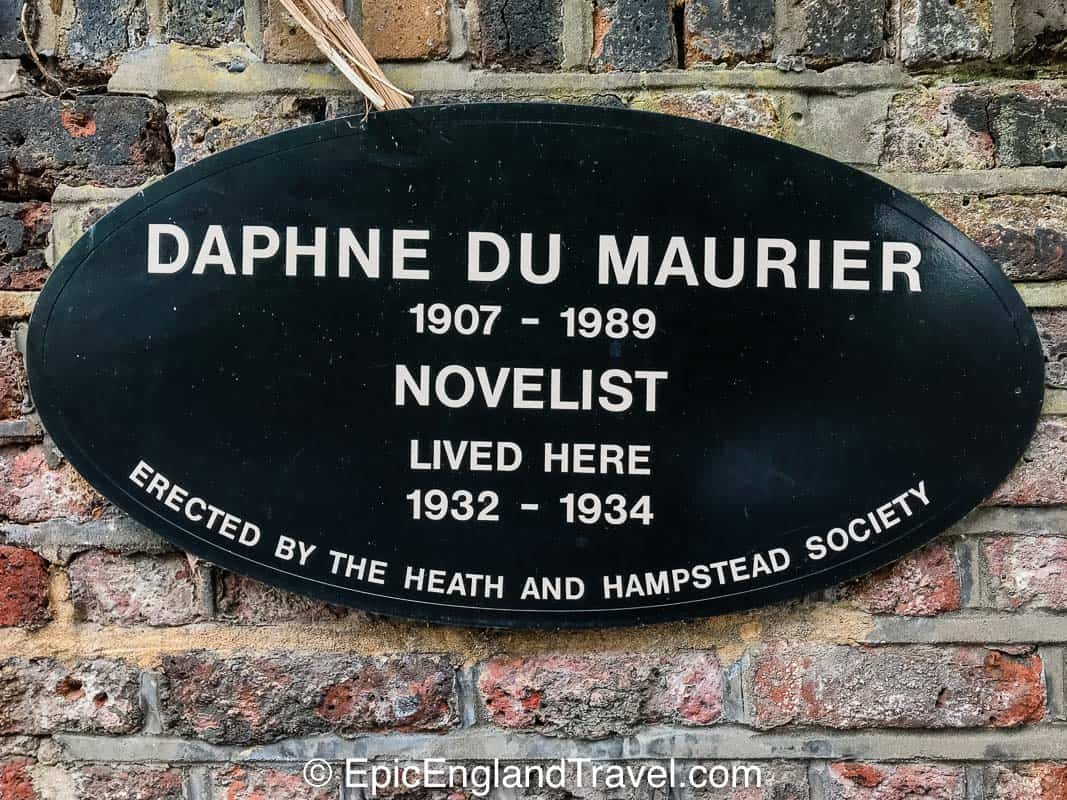 A badge on the side of a building in Hampstead indicating the novelist Daphne du Maurier lived there in the past.