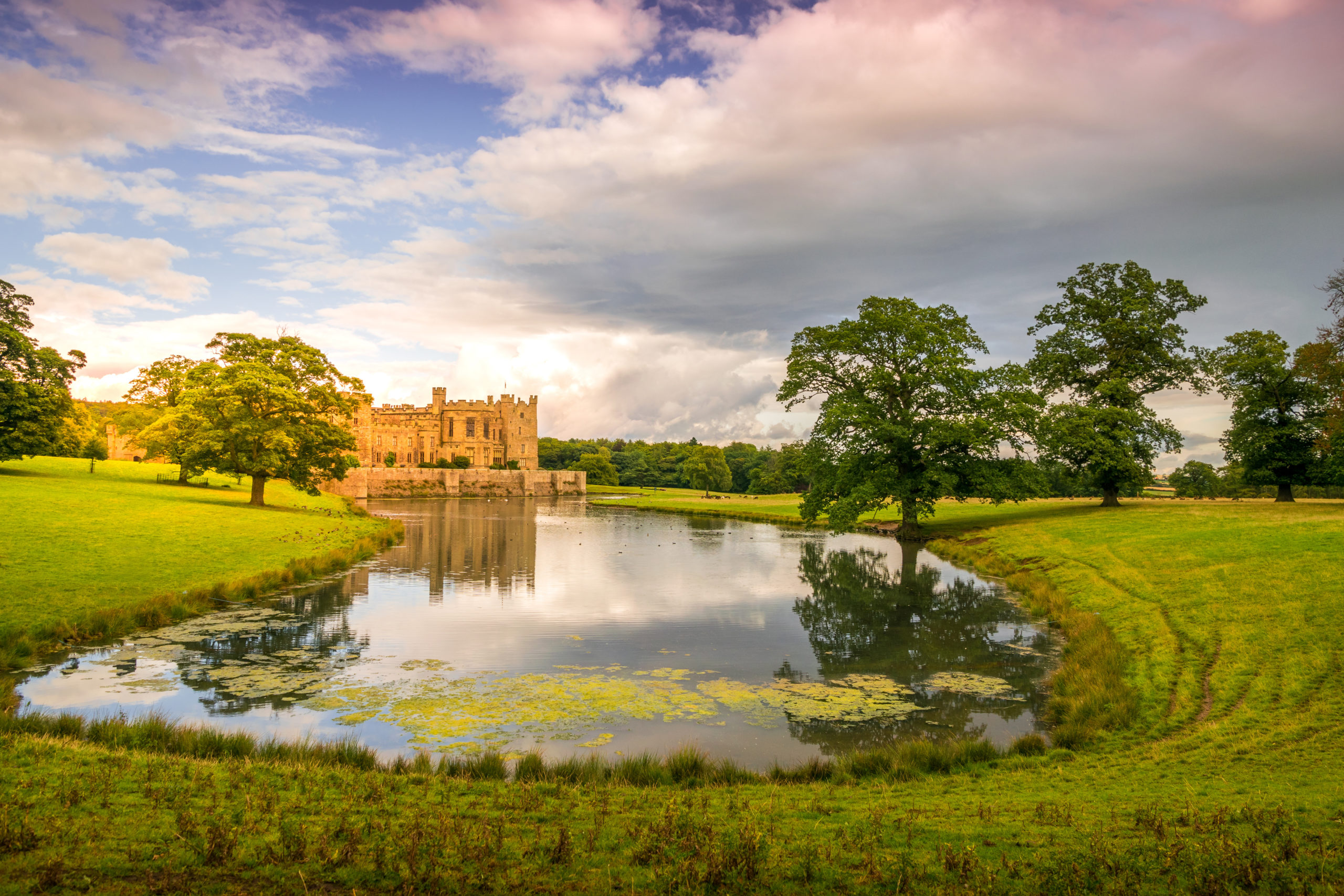 Raby Castle reflected in a pond and a parklike setting.