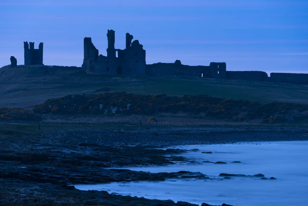 Dunstanburgh Castle on top of hill near body of water